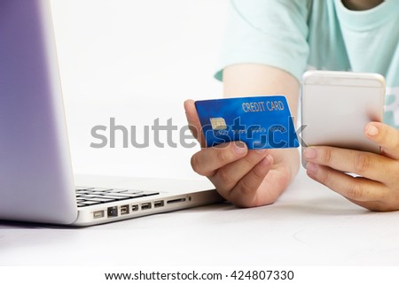 internet online shopping concept with credit card, shopping cart and blurred young woman using tablet in background - stock photo
