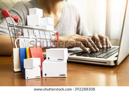 Internet online shopping concept with laptop and shopping-cart.Vintage tone retro filter effect,soft focus(selective focus)  - stock photo