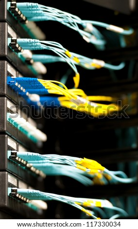Internet service provider equipment. Focus on panel with optic cables connected to panel in datacenter. Network server room. Modern technology. Yellow and blue cables contrast with dark background. - stock photo