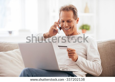 Internet shopping. Cheerful mature man shopping online while sitting on the couch at home - stock photo