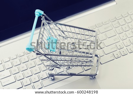 internet shopping concept - cart on computer keyboard