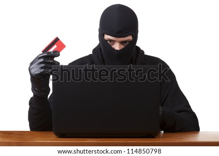 Internet Theft - a man wearing a balaclava and holding a credit card while sat behind a laptop, white background. - stock photo