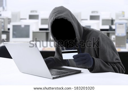 Internet Theft - a man wearing a balaclava and holding a credit card while sat behind a laptop,  - stock photo