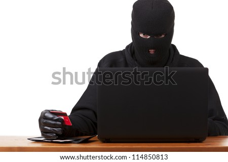 Internet Theft - a man wearing a balaclava holding a credit card sat behind a laptop, white background.