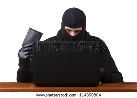 Internet Theft - a man wearing a balaclava holding a wallet while sat behind a laptop, white background.
