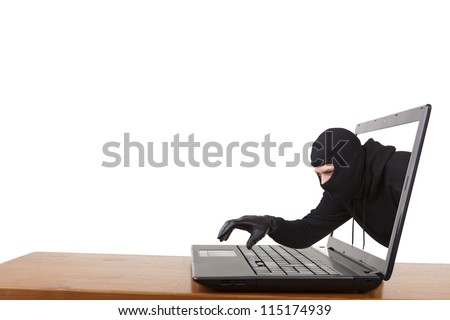 Internet theft  - a man wearing a balaclava reaching out through a laptop screen onto the keyboard.
