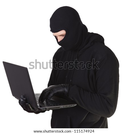Internet theft - a masked man with a laptop. - stock photo