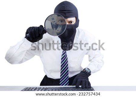 Internet Theft - businessman wearing mask and looking at computer screen using magnifying glass - stock photo