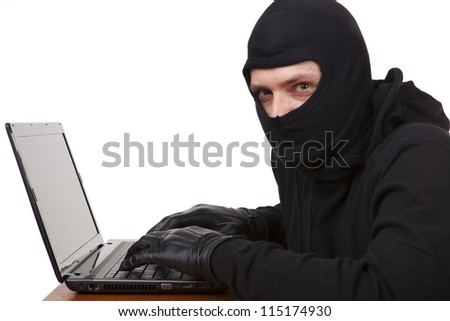 Internet theft - masked man sat behind laptop. - stock photo