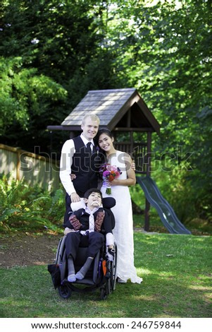 Interracial bride and groom standing with her disabled little boy in wheelchair for wedding pictures outdoors - stock photo