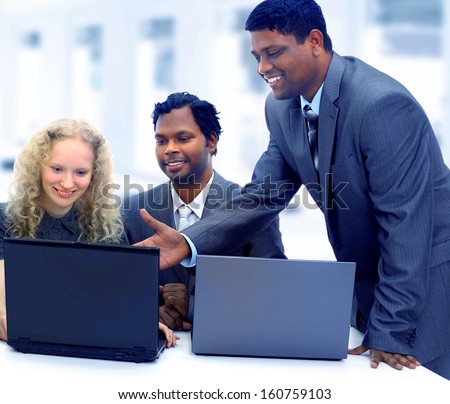 Interracial business team working at laptop in a modern office