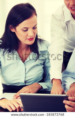 Interracial business team working at laptop in a office - stock photo