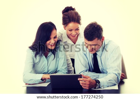 Interracial business team working at laptop in a office, isolated on white - stock photo