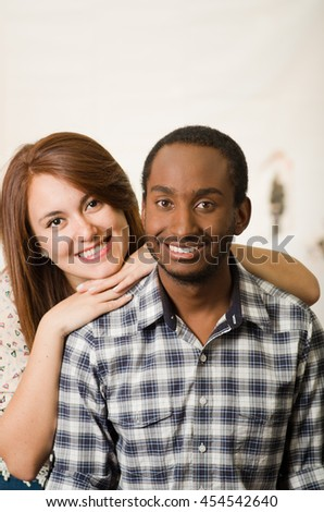 Interracial charming couple wearing casual clothes posing interacting friendly, white studio background - stock photo