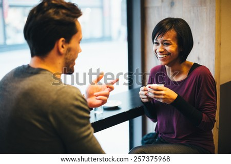 Interracial couple in love having fun in coffee shop - stock photo