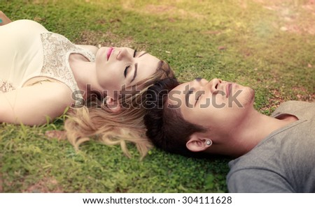 Interracial Couple Lovers Lying Down On The Grass - stock photo
