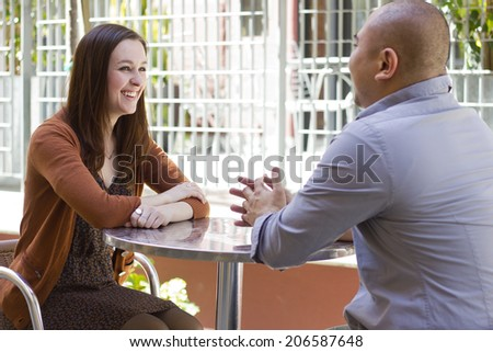 interracial couple meeting on a casual first date outdoors - stock photo