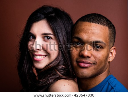 interracial couple smiling portrait on brown background - stock photo
