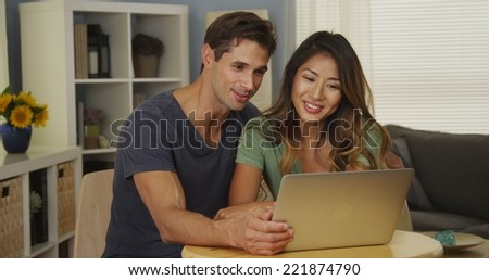 Interracial couple video chatting with family on laptop - stock photo