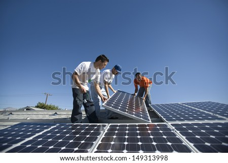 Interracial engineers positioning solar panel against clear blue sky