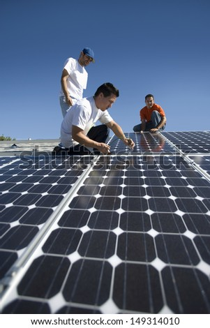 Interracial engineers working on solar panel against clear blue sky