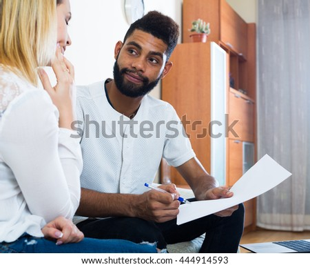 Interracial family couple filling papers for mortgage indoors