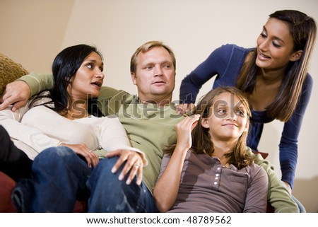 Interracial family of four sitting together on living room sofa in living room