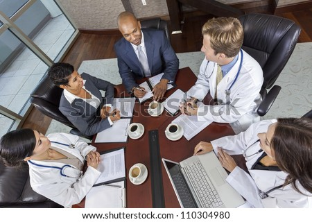 Interracial group of business men & women, businessmen and businesswomen and doctors team meeting in hospital boardroom - stock photo