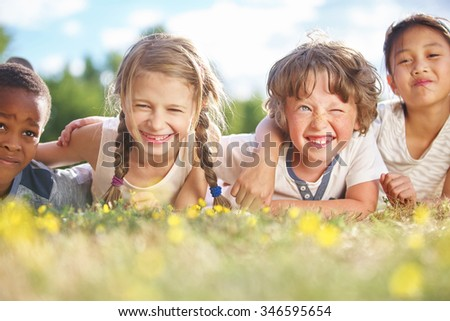 Interracial group of children in summer on the grass  - stock photo