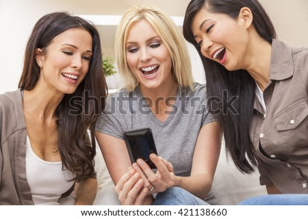 Interracial group of three beautiful young women friends at home laughing using a smart phone at home - stock photo
