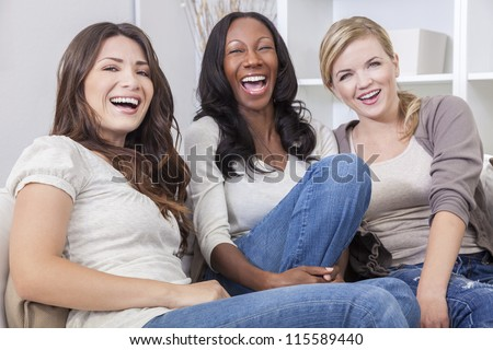 Interracial group of three beautiful young women friends at home sitting together on a sofa smiling and having fun - stock photo