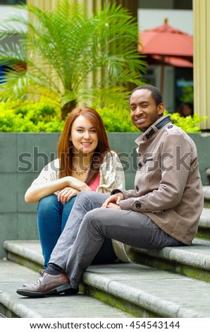 Interracial happy charming couple sitting on steps in front of building interacting and smiling for camera - stock photo