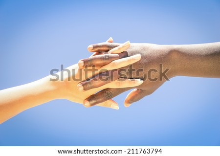 Interracial human hands crossing fingers for friendship and love - Concept of peace and unity against racism - Multi ethnic couple holding hands - stock photo