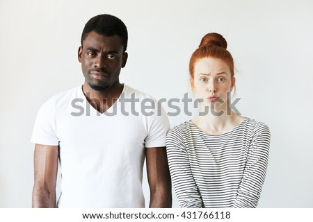 Interracial love and friendship. African male and redhead Caucasian woman looking at the camera with disappointment, having quarrel, displeased with each other. Portrait of young mixed-race couple - stock photo