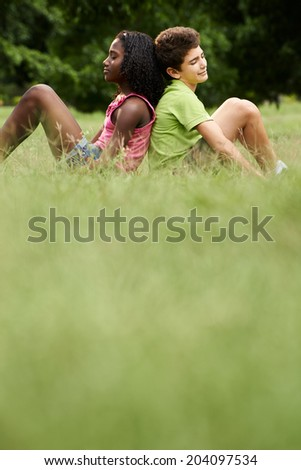 Interracial people in love with black little girl caucasian and boy, leaning back to back on grass in park - stock photo