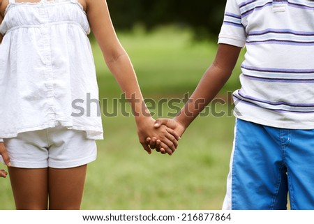 Interracial people in love with caucasian little girl and african boy holding hands in park. Cropped view - stock photo