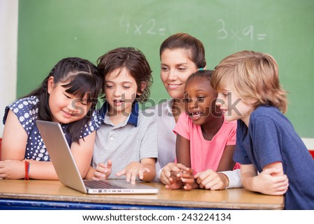 Interracial primary classroom learning to use laptop with their teacher. - stock photo