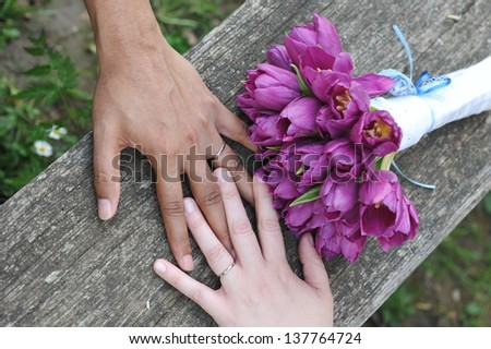 interracial wedding couple holding hands - stock photo