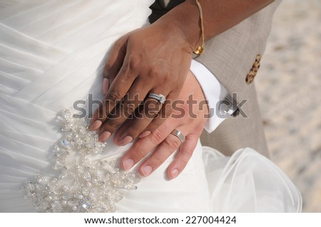 Interracial wedding couple put their hands together showing the rings - stock photo