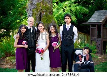 Interracial wedding. Groom standing with his biracial bride's brothers and sisters outdoors. Youngest boy is disabled with cerebral palsy. - stock photo