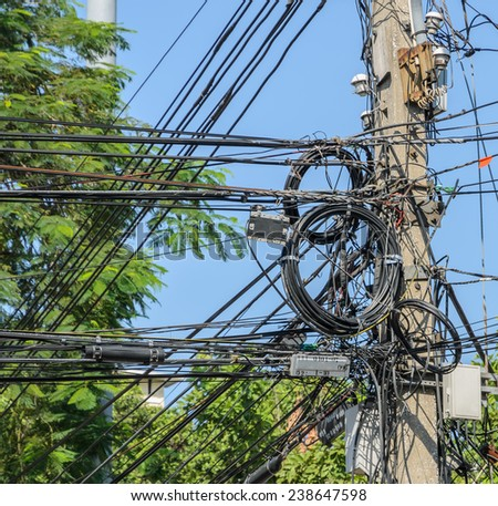 Intertwining of many electrical wires on pole, messy electric cables - stock photo