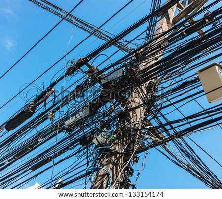 Intertwining of many electrical wires on poles - stock photo
