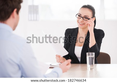 Interviewing a job candidate. Cheerful young woman in formalwear holding document and smiling while man sitting in front of her and gesturing - stock photo