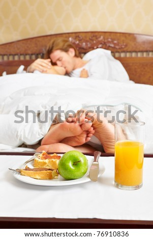 Intimate couple spending their time in bed and breakfast near their feet