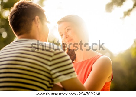 Intimate moments - young couple hugging in nature against sun - stock photo