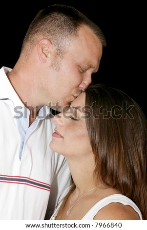 Intimate portrait of a young couple in love.  He is kissing her tenderly on the forehead. - stock photo