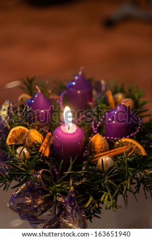 Intimate view of purple christmas wreath with one burning candle. - stock photo