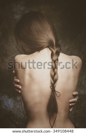 intimate woman portrait, bare back and long braid, natural blond hair, studio shot