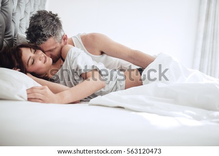 Intimate young couple enjoying sensual foreplay on bed. Man kissing on neck of woman.