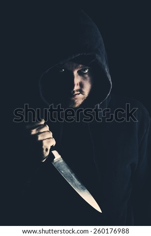 Intimidating Hooded Youth Clutching Knife to Chest  - stock photo